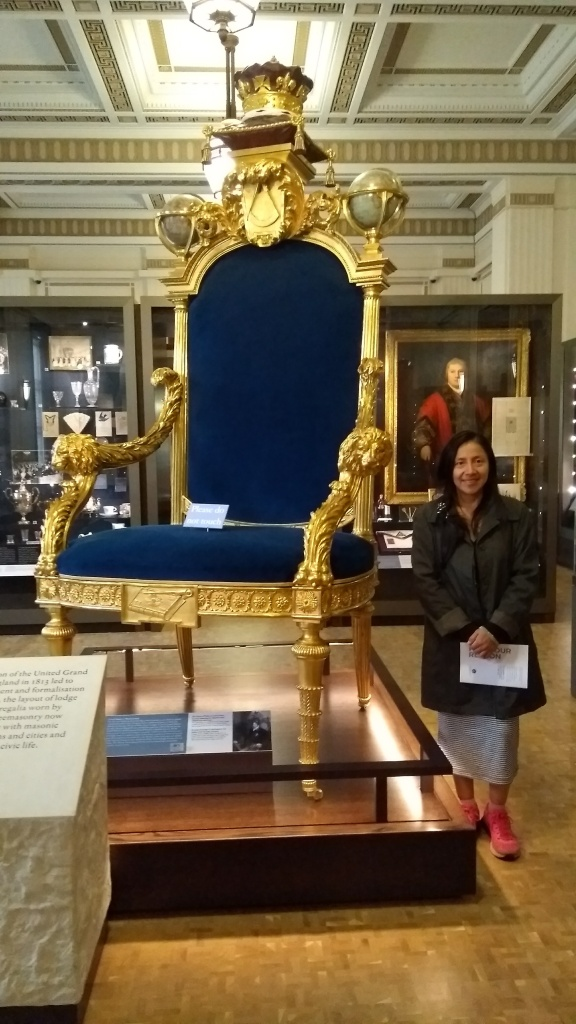 Small girl standing next to chair to show size of golden chair.